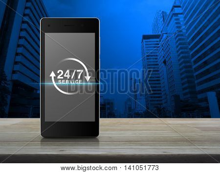 24 hours service icon on modern smart phone screen on wooden table in front of city tower background Full time service concept