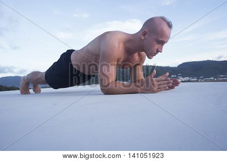 Bottom side view of handsome muscular man doing plank push up exercise on a rooftop over blue sky and green mountains tops. Sport and healthy lifestyle concept