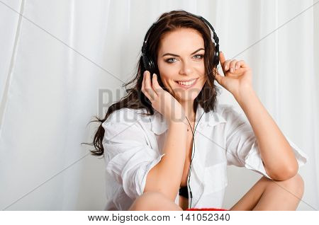 Happy beautiful, slim, attractive brunette woman in Bello shirt and short shorts sitting on the bed and listening to music on headphones