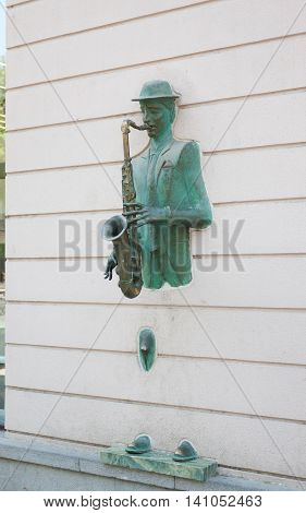 TBILISI, GEORGIA - AUGUST  7,2013 : Bronze statue of saxophonist coming through the wall on Rustaveli street in old Tbilisi, Georgia