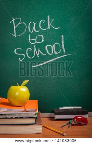 Teacher's desk with a pile of books, an apple and other equipment.  The words 'Back to School' written in chalk on the blackboard in soft focus background