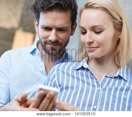 Closeup photo of young couple using mobile.