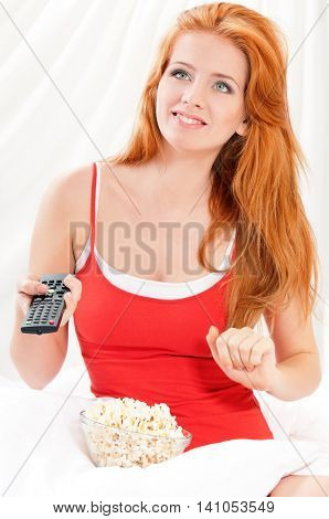 Young beautiful happy girl watching movie or tv in bed and eating  popcorn