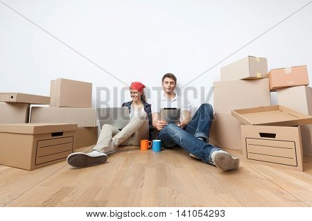 Young Couple Sitting on the Floor with Boxes and Using a Laptop and a Tablet