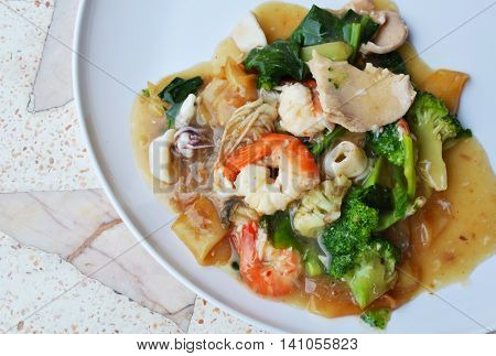 stir-fried large noodle with seafood in gravy sauce on plate
