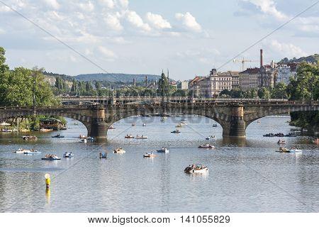 PRAGUE, CZECH REPUBLIC, JULY 5,2016: People having fun with pedalos on Vltava River, Legion Bridge on the background.