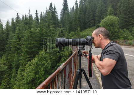 Professional nature photographer shooting with camera on tripod