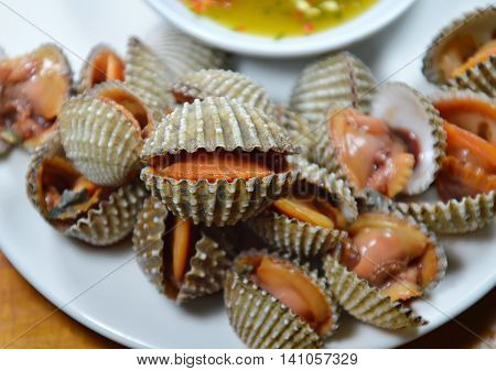 steamed cockle with spicy dipping sauce on dish