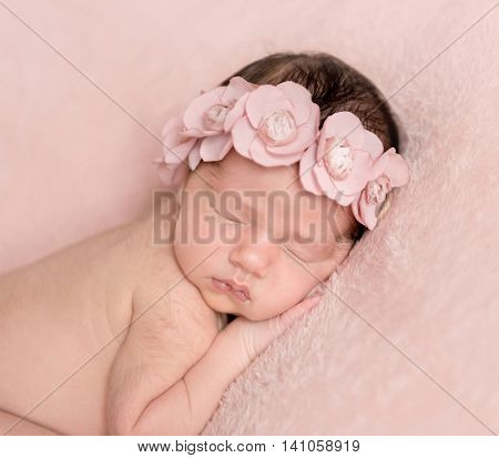 infant girl sleeping on a pink background close-up