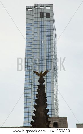 sculpture of an eagle and a multi-storey building of glass. monument
