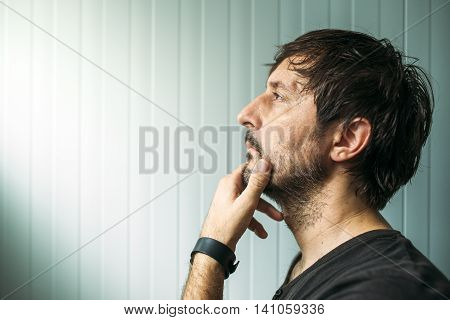 Pensive unshaven man with hand on chin making decision judging or evaluating something studio profile portrait with copy space
