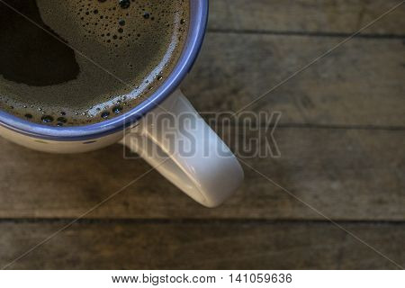 Black coffee in a cup on a wooden floor.