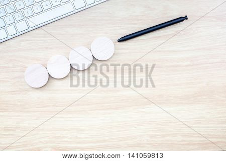 Black Pen Pointing At Four Piece Of Round Wood With Keyboard On Wooden Table , Mock Up For Adding Yo