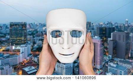 Hands holding white mask on blurred city landscape background.