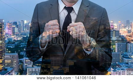 Double exposed of businessman holding his fists in front of him with cityscape at night.