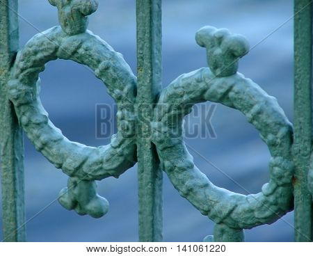 cast iron decorative fence along the river. green steel fence