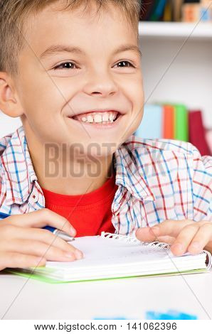 Young smiling boy sitting at desk in the classroom, doing homework at the table