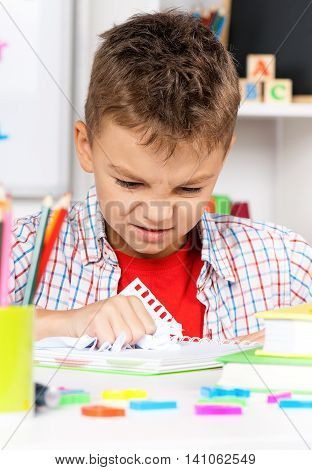 Young, sad boy sitting at desk in the classroom with piece of crushed paper