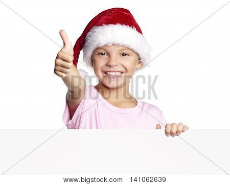 Happy little Santa Claus. Smiling Christmas little boy in red Santa hat peeking from blank board, isolated on white background. Space for text.