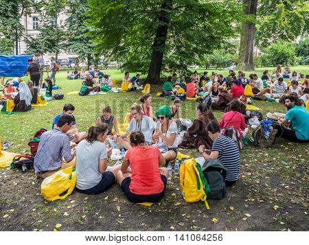 KRAKOW POLAND - JULY 29 2016:. World Youth Day 2016. Young people from various countries sitting on the ground resting eating drinking and talking in small groups in Planty Park in Cracow near the railway station
