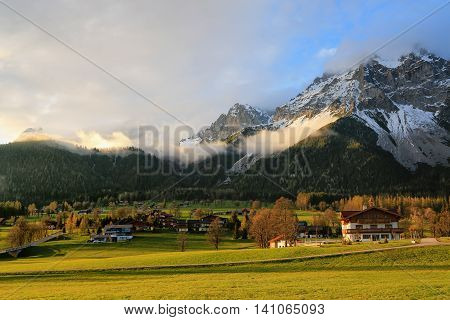 The picturesque village in the foothills of the Alpine peaks on a spring day beautifully colored meadows evening sun Austria Dachstein