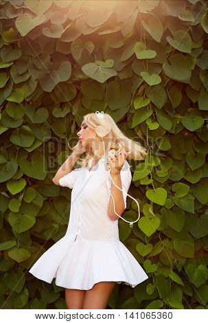 Young blonde woman dancing in a green leaves while listening to music with her headphones. Girl listening to music streaming with headphones and dancing on nature background.