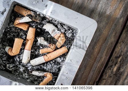 Smoked Cigarettes Butts in ashtray on the table.
