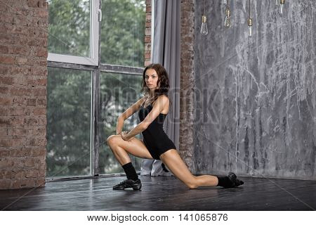 Dance. Professional ballet dancer in training black uniform stretched before the performance. Art concept. Young brunette girl warming up before dance. Slim and plastic dancer exercising