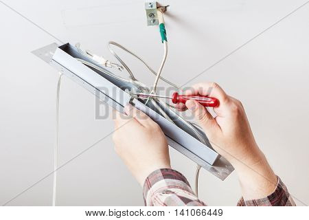 Electrician Installs Wiring In Ceiling Lamp