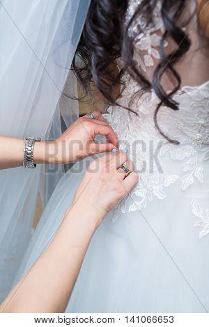 bridesmaid tying bow on white wedding dress
