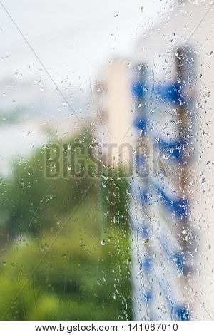 Raindrops On Window And Blurred Apartment Houses