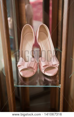 Stylish fashion pink high heels with a bow on the background room glamor bridal wedding