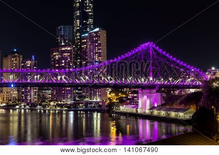 BRISBANE, AUSTRALIA: Brisbane Story Bridge northern side (magenta) and cityscape closeup by night viewed from the New Farm Riverwalk