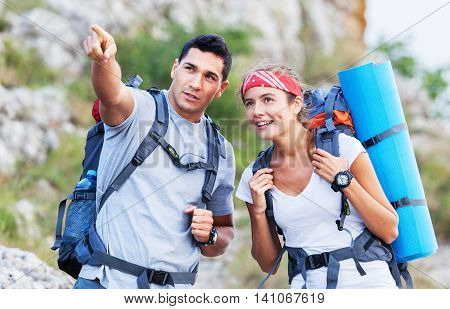 Hiking people. A couple of hikers pointing looking at nature in beautiful landscape mountains of Yosemite National Park, California, USA. Young multiracial couple on hike, Caucasian man, Asian woman