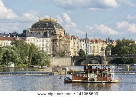 PRAGUE, CZECH REPUBLIC, JULY 5,2016: A modern steamboat cruising on Vltava River, Legion Bridge and National Theatre can be seen on the background.