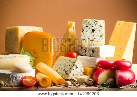 Various Kinds of Cheeses on the Wooden Platter - on the Brown Background