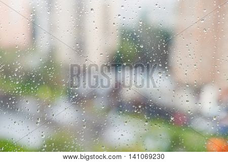 Raindrops On Window And Blurred Houses