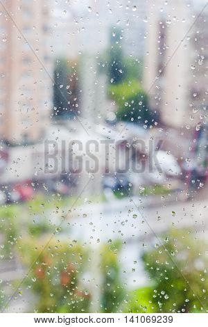 Rain Drops On Window Glass And Blurred Cityscape