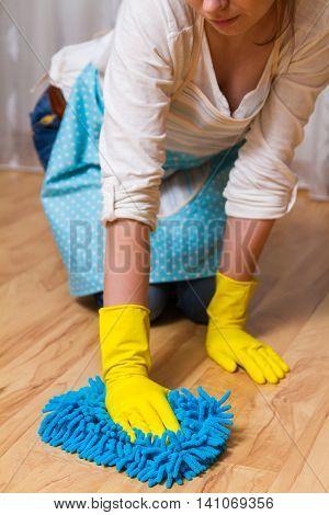 Wash wood floor concept. Young woman wipes the floor with a cloth gloves, sitting on his lap