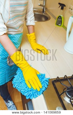 Kitchen cleaning concept. Female hands in gloves closeup