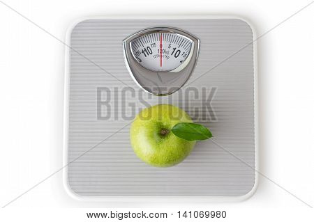Green apple on a bathroom scale - weight loss/dieting concept