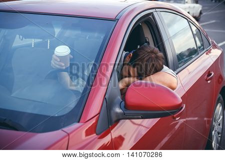 Young man while driving drinks cofee, bored in traffic