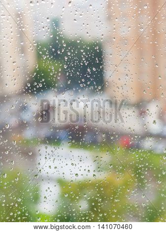 raindrops on window and blurred cityscape on background