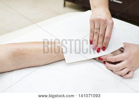 Woman in a beauty salon doing depilation