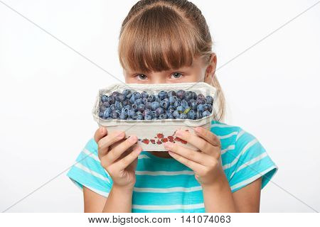Smiling girl holding a box with bilberries, over white background