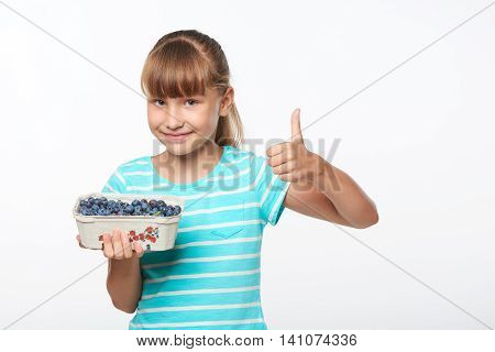 Smiling girl holding a box with bilberries and gesturing thumb up, over white background