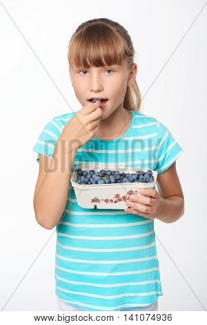 Little girl holding a box with bilberries and eating it, over white background