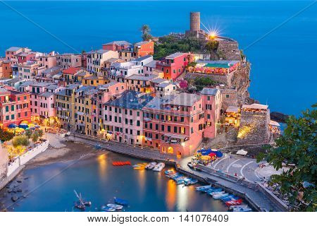 Aerial Night fishing village Vernazza with lookout tower of Doria Castle to protect the village from pirates, Five lands, Cinque Terre National Park, Liguria, Italy.