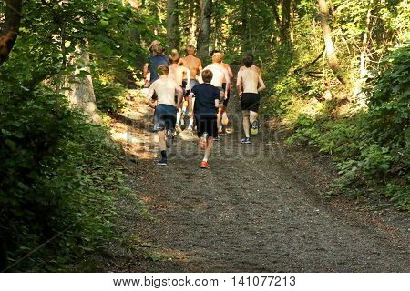 a boys cross country team workouts running up a hill in the trails