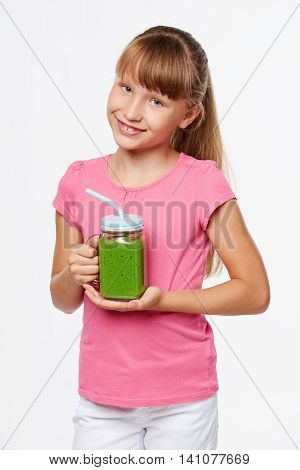 Happy smiling girl holding jar tumbler mug with green smoothie drink over white background